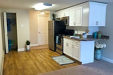 Newly remodeled kitchen in our Sunrise floor plan featuring granite-style countertops, wood-style flooring, and ample cabinet space.