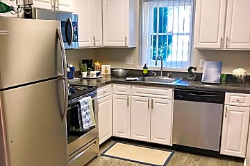Our newly remodeled kitchens feature black fusion counter tops, grey wood-style flooring, and stainless steel appliances.