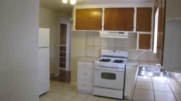 Kitchen with gas range and fridge.