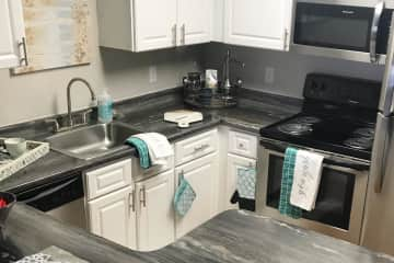 Updated kitchens with black fusion countertops, wood-style flooring, and stainless steel appliances.