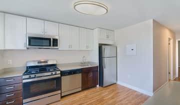 Modern kitchen features quartz countertops and designer cabinets