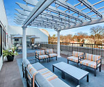 Our outdoor lounge features both table and lounge seating under a pergola with string lights and speakers, Waldwick Station