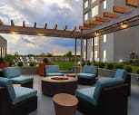 Hang out on the 4th floor courtyard with a grilling station, fire pit, wall-mounted TV, and spacious green area, One Ardmore
