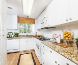kitchen featuring natural light, refrigerator, gas range oven, dishwasher, microwave, light hardwood flooring, light stone countertops, and white cabinets, Santa Maria
