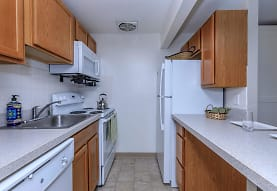 kitchen with refrigerator, electric range oven, dishwasher, microwave, light countertops, light tile floors, and brown cabinets, Autumn Ridge Studio