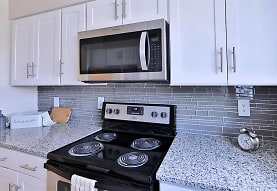 kitchen featuring electric range oven, stainless steel microwave, light stone countertops, and white cabinets, Mount Vernon Square Apartments