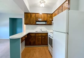 kitchen with refrigerator, range oven, light hardwood flooring, brown cabinets, and light countertops, Eastlake Terrace & Maple Park Apartments