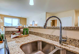 kitchen with natural light, light flooring, dark brown cabinets, and light stone countertops, Copper Creek Apartments