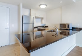 kitchen with a center island, lofted ceiling, refrigerator, range hood, microwave, white cabinetry, dark stone countertops, and light tile floors, Liberty Tower