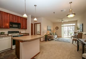 kitchen with a kitchen island, carpet, natural light, a ceiling fan, dishwasher, electric range oven, microwave, light floors, pendant lighting, brown cabinets, and light countertops, Prospect Commons