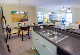 kitchen featuring carpet, a ceiling fan, a wealth of natural light, refrigerator, dishwasher, dark granite-like countertops, pendant lighting, white cabinets, and light flooring, Sugar Mill