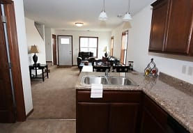 kitchen with carpet, dishwasher, granite-like countertops, dark brown cabinetry, and pendant lighting, Tioga Townhomes
