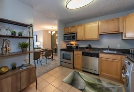 kitchen featuring washer / dryer, electric range oven, stainless steel appliances, light brown cabinetry, dark stone countertops, pendant lighting, and light tile floors, The Point at Pentagon City