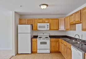 kitchen featuring electric range oven, refrigerator, dishwasher, microwave, light tile floors, dark countertops, and brown cabinets, Legacy Park Apartments