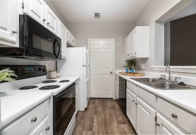 kitchen featuring electric range oven, dishwasher, microwave, white cabinets, light countertops, and dark hardwood floors, Walden Pond