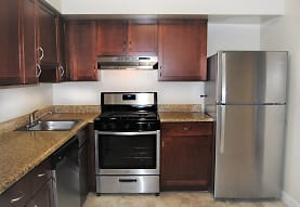 kitchen featuring exhaust hood, stainless steel refrigerator, gas range oven, dishwasher, dark granite-like countertops, light tile flooring, and dark brown cabinets, The Apartments at Bonnie Ridge