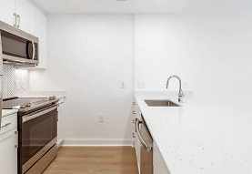 kitchen featuring stainless steel microwave, refrigerator, electric range oven, dishwasher, white cabinetry, light stone countertops, and light parquet floors, Liberty Tower
