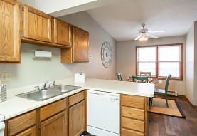 kitchen with natural light, a ceiling fan, dishwasher, dark hardwood floors, brown cabinets, and light countertops, Creekstone Falls