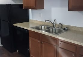 kitchen featuring refrigerator, dishwasher, light countertops, brown cabinets, and dark hardwood flooring, Pier 39 Apartments & Townhomes