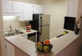 kitchen with refrigerator, dishwasher, dark flooring, white cabinets, and light countertops, Audubon Lake Apartment Homes
