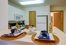 kitchen featuring refrigerator, microwave, range oven, white cabinets, and light countertops, Hawks Ridge