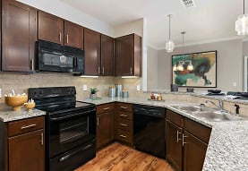 kitchen featuring dishwasher, electric range oven, microwave, light hardwood floors, pendant lighting, dark brown cabinets, and light stone countertops, Lakeside Village