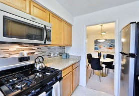 kitchen featuring stainless steel microwave, refrigerator, brown cabinets, pendant lighting, light tile floors, and light stone countertops, Mount Vernon Square Apartments