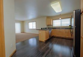 kitchen with natural light, refrigerator, dishwasher, dark countertops, pendant lighting, brown cabinets, and dark hardwood flooring, Griffin Court Apartment Community
