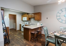 kitchen featuring a ceiling fan, a breakfast bar area, refrigerator, electric range oven, baseboard radiator, microwave, dark parquet floors, light countertops, and brown cabinets, Creekstone Falls