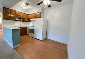 kitchen featuring a ceiling fan, refrigerator, range oven, fume extractor, light countertops, light hardwood floors, and brown cabinetry, Eastlake Terrace & Maple Park Apartments