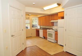 kitchen featuring electric range oven, refrigerator, extractor fan, dishwasher, dark countertops, light tile floors, and brown cabinets, The Larkspur