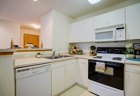 kitchen with electric range oven, dishwasher, microwave, white cabinetry, and light tile flooring, Hawks Ridge