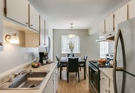 kitchen with natural light, range hood, stainless steel refrigerator, electric range oven, light hardwood floors, pendant lighting, white cabinets, and light countertops, Bloomfield Square Apartments