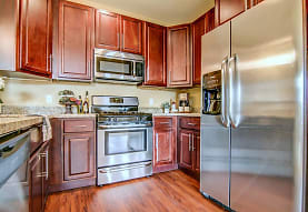 kitchen with stainless steel appliances, range oven, light stone countertops, light parquet floors, and dark brown cabinets, Copper Creek Apartments