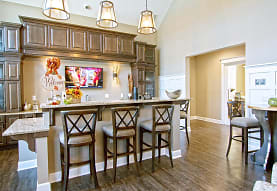 kitchen featuring a breakfast bar, dark hardwood floors, stone countertops, pendant lighting, and dark brown cabinetry, The Ravines at Westar