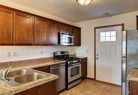 kitchen featuring natural light, stainless steel appliances, gas range oven, stone countertops, dark brown cabinetry, and dark tile floors, Tioga Townhomes