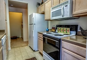 kitchen with stainless steel microwave, refrigerator, electric range oven, dishwasher, light countertops, light tile flooring, and brown cabinets, Audubon Lake Apartment Homes