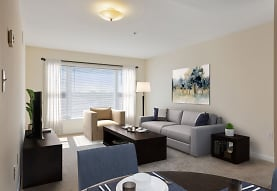 carpeted living room featuring natural light and TV, Legacy Park Apartments