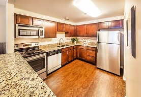 kitchen featuring electric range oven, stainless steel appliances, dark stone countertops, dark brown cabinets, and light parquet floors, Grandin House