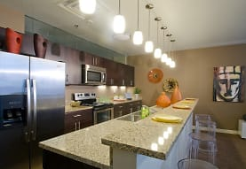 kitchen featuring a kitchen bar, stainless steel appliances, electric range oven, pendant lighting, dark brown cabinetry, light granite-like countertops, and dark floors, River Vue