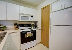 kitchen with refrigerator, electric range oven, microwave, light tile floors, white cabinets, and light countertops, Hawks Ridge