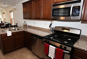 kitchen with stainless steel appliances, gas range oven, pendant lighting, light tile flooring, light granite-like countertops, and dark brown cabinets, Tioga Townhomes