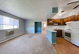 kitchen with carpet, natural light, a ceiling fan, range hood, baseboard radiator, refrigerator, gas range oven, light floors, dark brown cabinetry, and light countertops, Eastlake Terrace & Maple Park Apartments