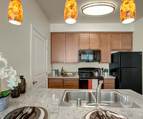 A kitchen with a deep double sink, lots of pantry space, and stone countertops, Solara Apartments