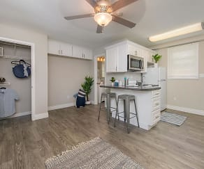 Spacious, open living area with wood-style flooring and closets with organizers., The Courtyards