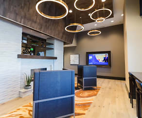 Cozy, modern resident lounge with stunning lighting, a fireplace, lounge seating, at TV and work space, Skyhouse Frisco Station
