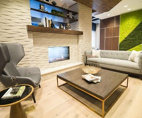 Cozy, modern resident lounge with stunning lighting, a live green wall, a fireplace, lounge seating, at TV and work space, Skyhouse Frisco Station
