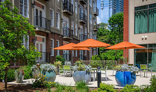 Eat on the outdoor patio equipped with tables and umbrellas, 1045 on the Park Apartment Homes