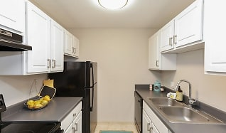 Galley style kitchen with all black appliances at Equinox Apartments, Equinox Apartments