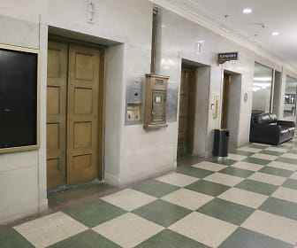 Ornately carved bronze elevator doors adorn the corridor., Commodore Perry